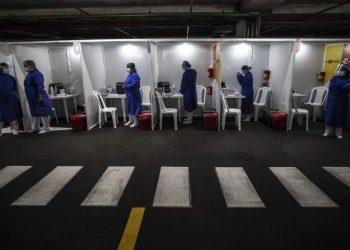 Los trabajadores de la salud se preparan para inocular a las personas con una dosis de la vacuna CoronaVac de Sinovac Biotech contra COVID-19, en el estacionamiento del Aeropuerto Internacional El Dorado en Bogotá, el 16 de julio de 2021. FOTO / AFP