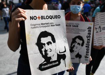 La gente sostiene carteles con la imagen del empresario colombiano Alex Saab, quien se encontraba distanciado a Estados Unidos, durante una manifestación exigiendo su liberación, en la plaza Bolívar de Caracas, el 17 de octubre de 2021. FOTO / AFP